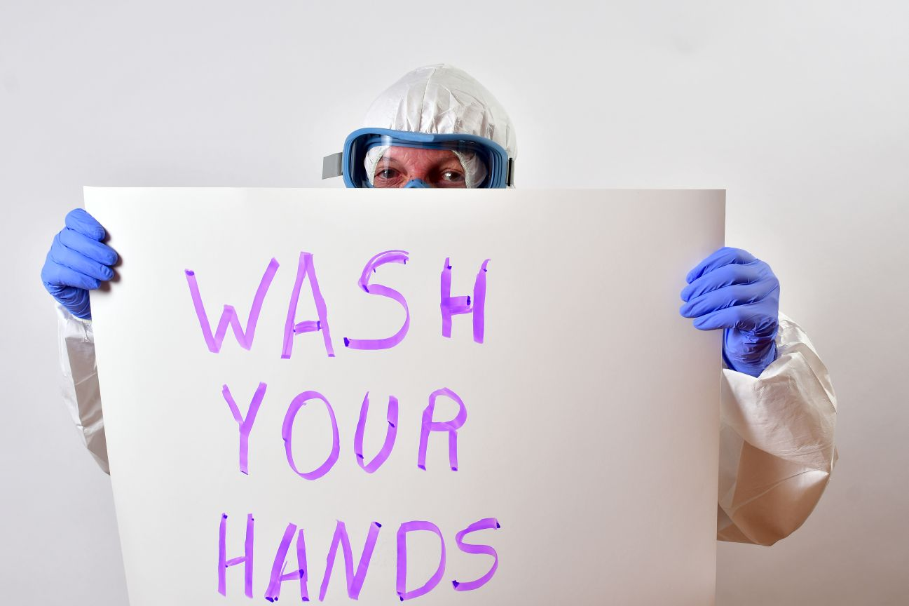 Man holding a sign that says 'wash your hands'
